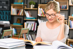 Young woman at the desk with lots of books Royalty Free Stock Photography