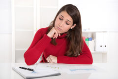 Young woman at desk with a red pullover. Royalty Free Stock Photo