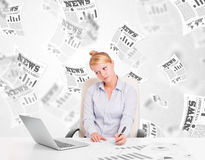 Young woman at desk with stock market newspapers concept Stock Photography