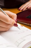 Young woman at desk writing a note (shallow dof). Royalty Free Stock Images