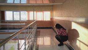 Young woman desperate to sit down on a wall in an empty corridor. stock video