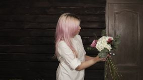 Young woman determines the design of a bouquet and composition holding a set of flowers. Next to the table is a variety. Of flowers for work stock video footage