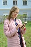 The young woman dials the phone number on the smartphone.  royalty free stock image