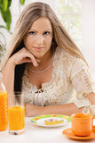 Young woman on diet. Sitting at table, thinking over tape measure on plate stock photos