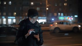 Young woman with digital tablet in evening city. Slow motion shot of a young smiling woman using digital tablet in the street. Car traffic of evening city in stock footage