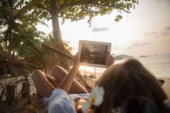 Young woman with digital tablet on hammock Royalty Free Stock Image