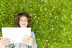 Young woman with digital tablet lying on grass Stock Photography