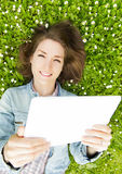 Young woman with digital tablet lying on grass Stock Image