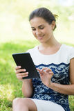 Young woman with digital tablet in park Stock Image