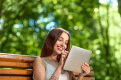 Young woman with digital tablet in the park Royalty Free Stock Photos