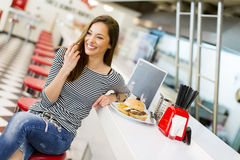 Young woman in the diner. View of the young woman eating in the diner royalty free stock image