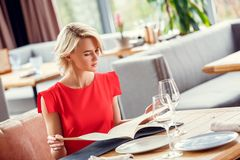 Young woman dining in restaurant sitting choosing dish from menu curious. Young woman dining at restaurant sitting at table looking at pages of menu choosing royalty free stock photos