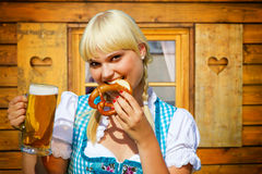 Young woman in a dirndl. Young woman with beer and pretzel on the alps stock images