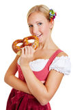 Young woman in dirndl biting in pretzel. Young happy smiling woman in a dirndl biting in a pretzel Royalty Free Stock Photo