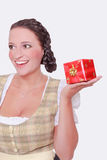Young woman in Dirndl and braided hair has a gift on the palm of her hand Royalty Free Stock Photography