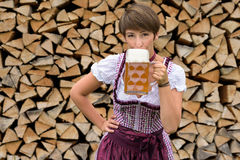 Young woman in a dirndl drinking a cold beer. Young woman in a traditional Bavarian dirndl standing in front of a neat woodpile drinking a cold beer royalty free stock photos
