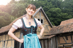 Young woman in dirndl in front of old farm houses. Portrait of young woman in dirndl in front of old farm houses stock image
