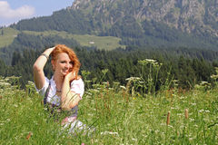 A young woman in the dirndl. A young girl in the dirndl sits laughing in a mountain pasture stock photo