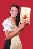 Young woman with dirndl and a great gift in hand Stock Photos