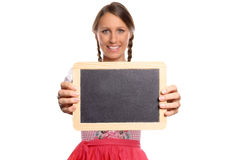 Young woman in a dirndl holding up a blank slate Royalty Free Stock Images