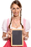 Young woman in a dirndl holding up a blank slate Royalty Free Stock Image