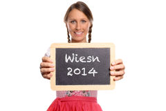 Young woman in a dirndl holding up a blank slate Stock Photos