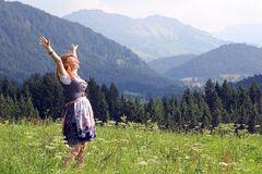 A young woman in the dirndl. A young woman in dirndl looking forward to a mountain meadow Stock Photos