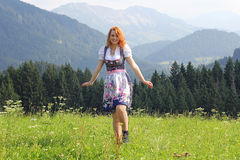 A young woman in the dirndl. A young woman in dirndl looking forward to a mountain meadow royalty free stock photo