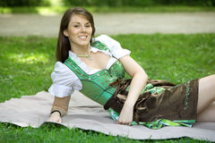 Young woman in dirndl lying on blanket outdoors. Young bavarian woman in dirndl lying on blanket in park royalty free stock images