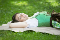Young woman in dirndl lying on blanket outdoors. Young woman in dirndl lying on blanket in grass royalty free stock image
