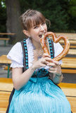 Young woman in dirndl with pretzel Stock Image