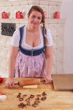 Young woman in dirndl rolling a dough with a rolling pin to bake cookies. Stock Photos