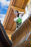 Young woman in dirndl standing on balcony. And looking down stock photo