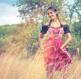 Young woman in dirndl walking alone in the field Royalty Free Stock Photos