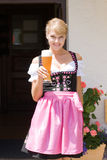 Young woman in dirndl with white beer. Young woman in dirndl wheat beer served in a mountain economy royalty free stock photography