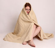 Young woman disaster survivor wrapped in a blanket Stock Images