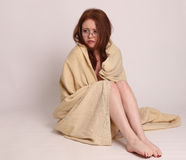Young woman disaster survivor wrapped in a blanket Stock Image