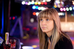 Young woman in a disco. Is sad Royalty Free Stock Photos
