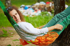 Young woman with discontented face lies in hammock at birchwood. Near pile of garbage stock image