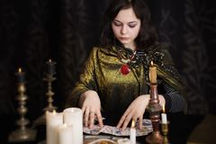 Woman with divination cards in room. Young woman with divination cards in room Royalty Free Stock Image