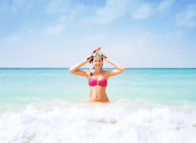 Young woman in a diving mask in the sea. Beautiful, cheerful young woman with diving mask being happy in the wavy water royalty free stock photography