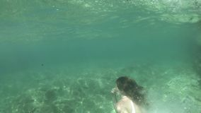 Slim young woman diving into the sea, underwater shot. Young woman diving into the sea stock video footage