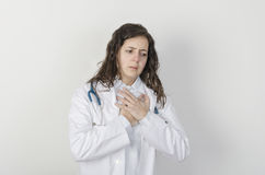 Young woman doctor is feeling pain in her heart. Stock Photography