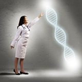 Young woman doctor finger glowing DNA symbol Stock Photo