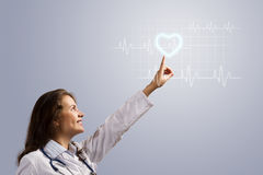Young woman doctor finger glowing heart symbol Royalty Free Stock Images