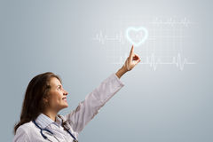 Young woman doctor finger glowing heart symbol Royalty Free Stock Image