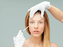 Young woman with doctor hands injecting botox Royalty Free Stock Photos
