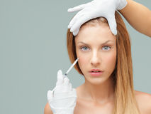 Young woman with doctor hands injecting botox Royalty Free Stock Photo
