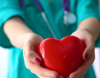 Young woman doctor holding a red heart, in office Stock Photography