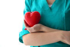 Young woman doctor holding a red heart, in office Royalty Free Stock Images
